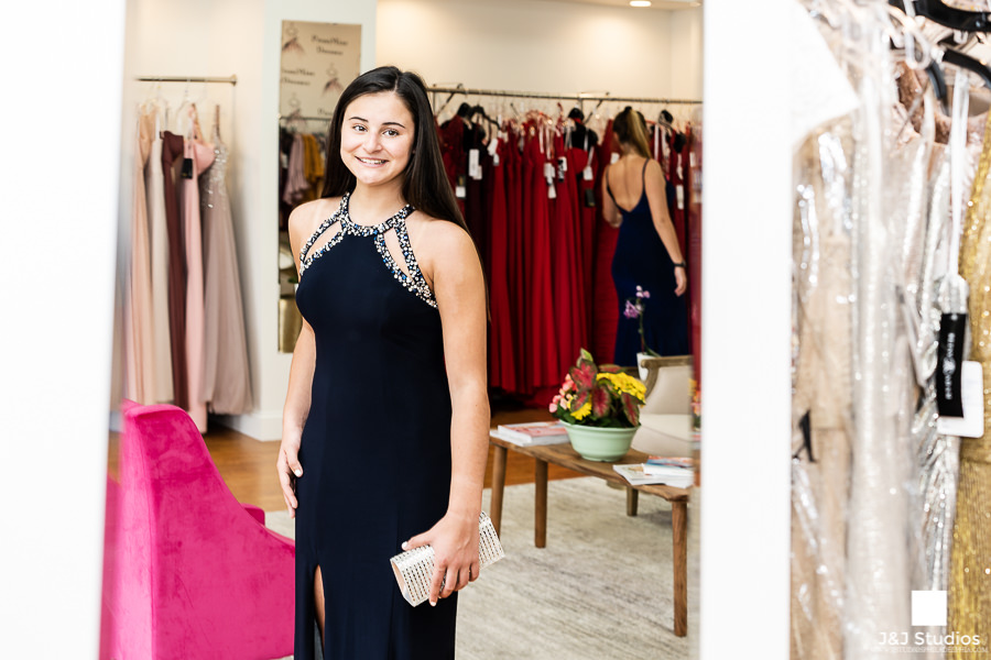 Customer looks at herself in the mirror at PromMiss Dresses.