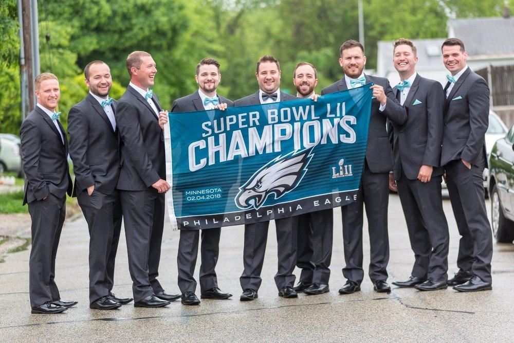 groomsmen-hold-eagles-flag-at-wedding
