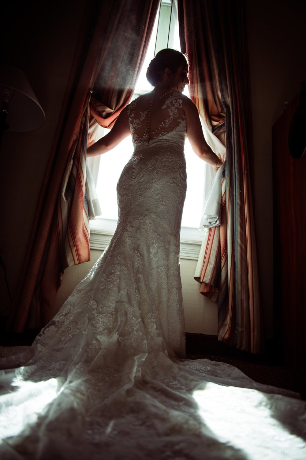 bride-opening-curtains-dramatic-shot