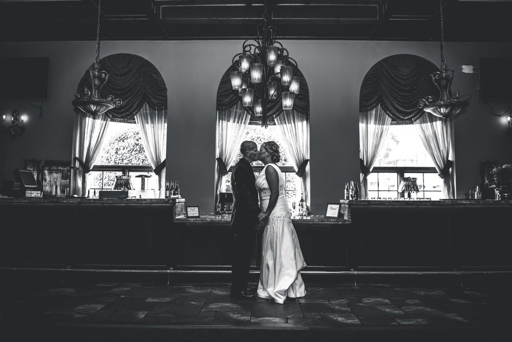 Here our couple shares a quick kiss before the ceremony and what better spot than at the bar.