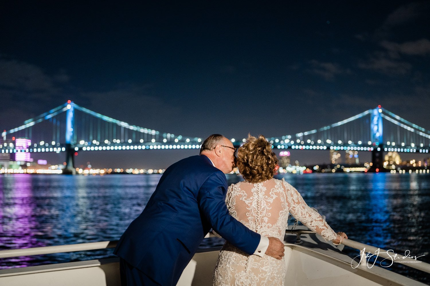 couple kissing on yacht ben franklin bridge in background
