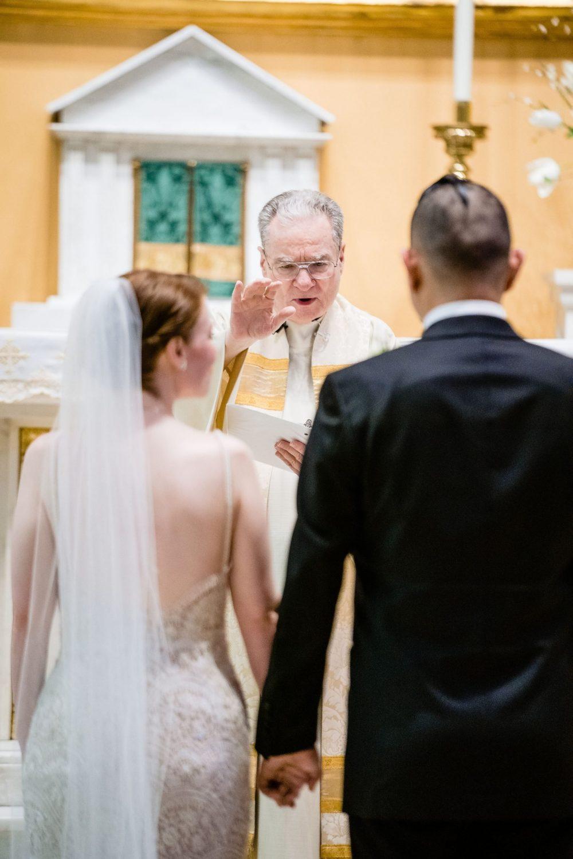 priest at wedding veil groom bride