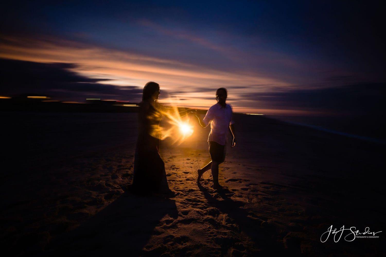 dark clouds sunlight sunset beach couple