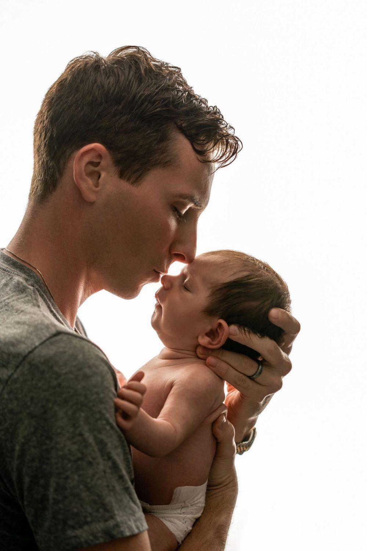 dad kissing newborn baby happy