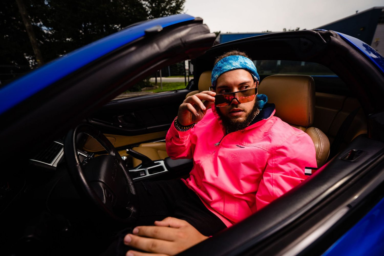 man sunglasses driving car coral jacket NYC photography