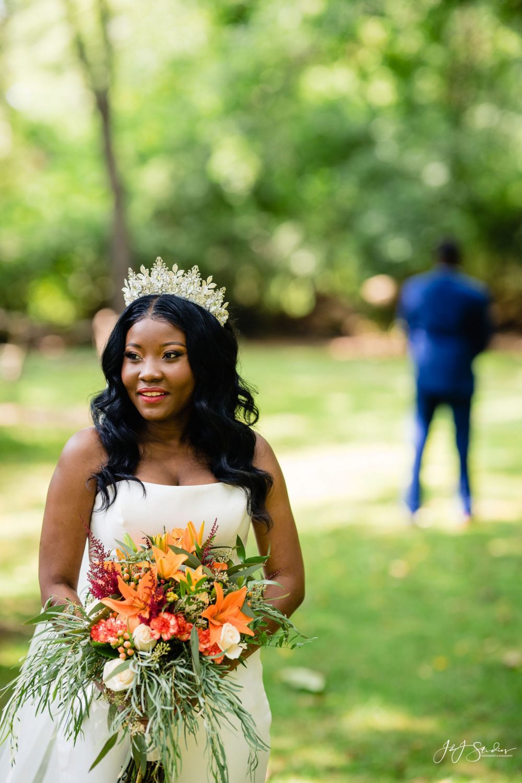 bouquet bride first look groom in background crown
