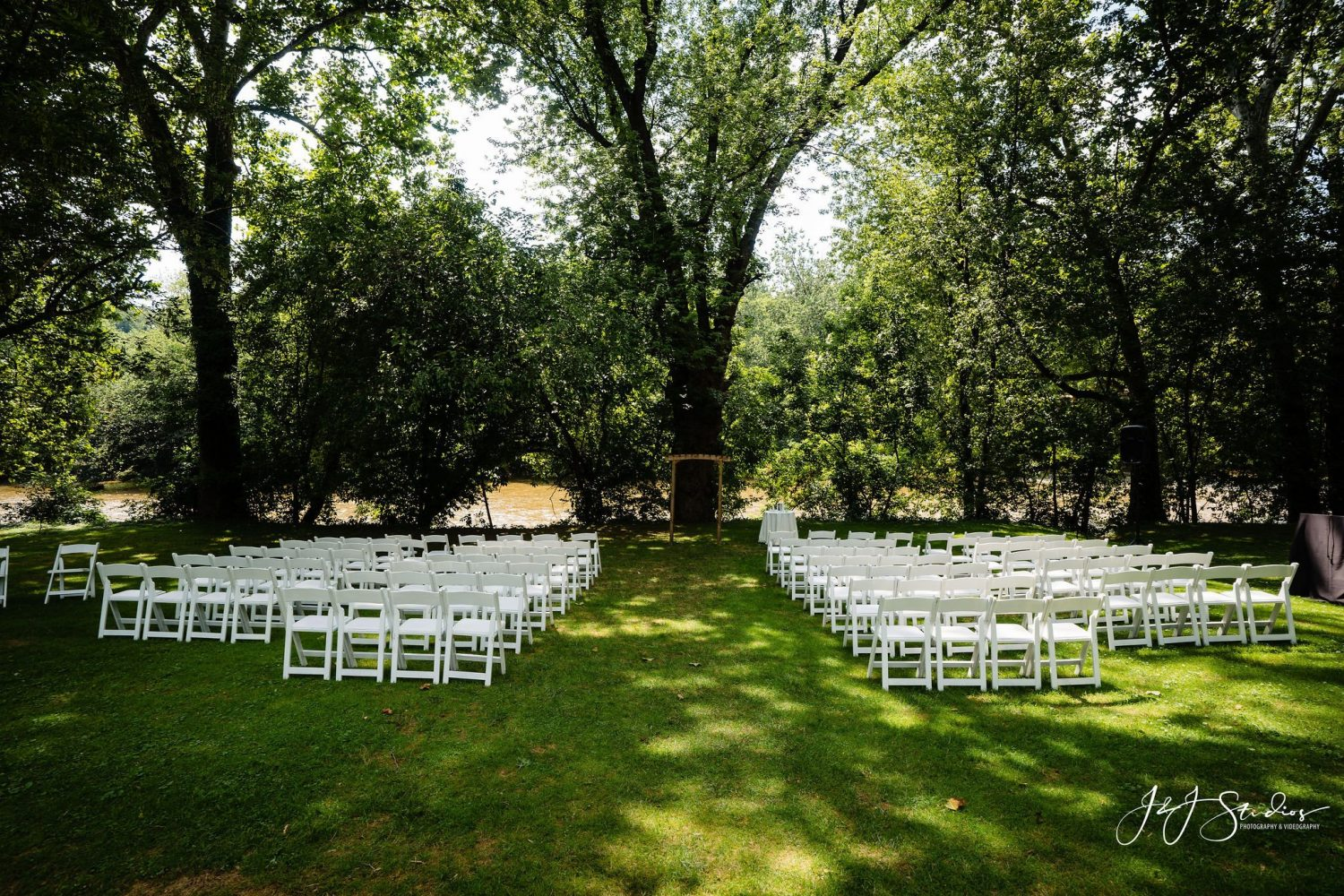 whiet chairs lawn trees sunlight beaming in ceremony wedding