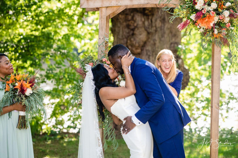 ceremony bride groom kissing white wedding dress blue tux