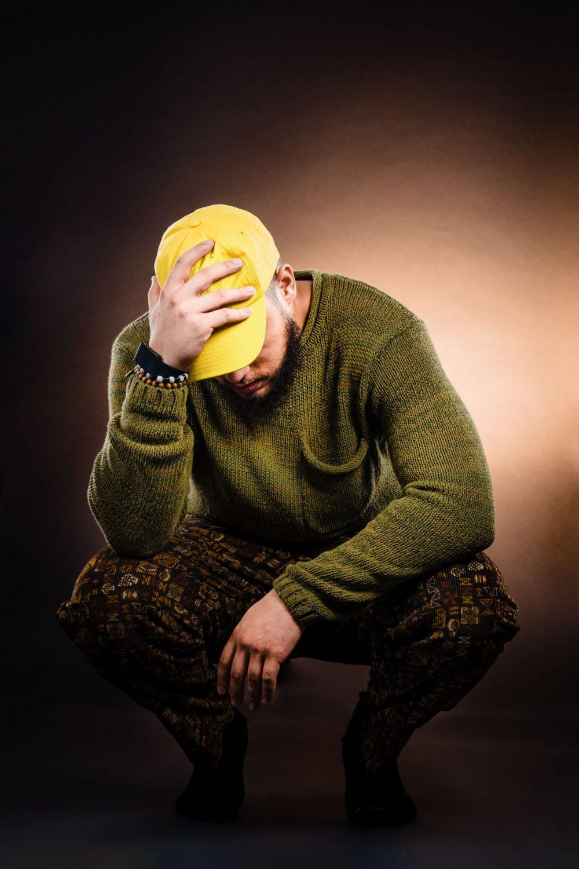 hand on head man green sweater yellow hat