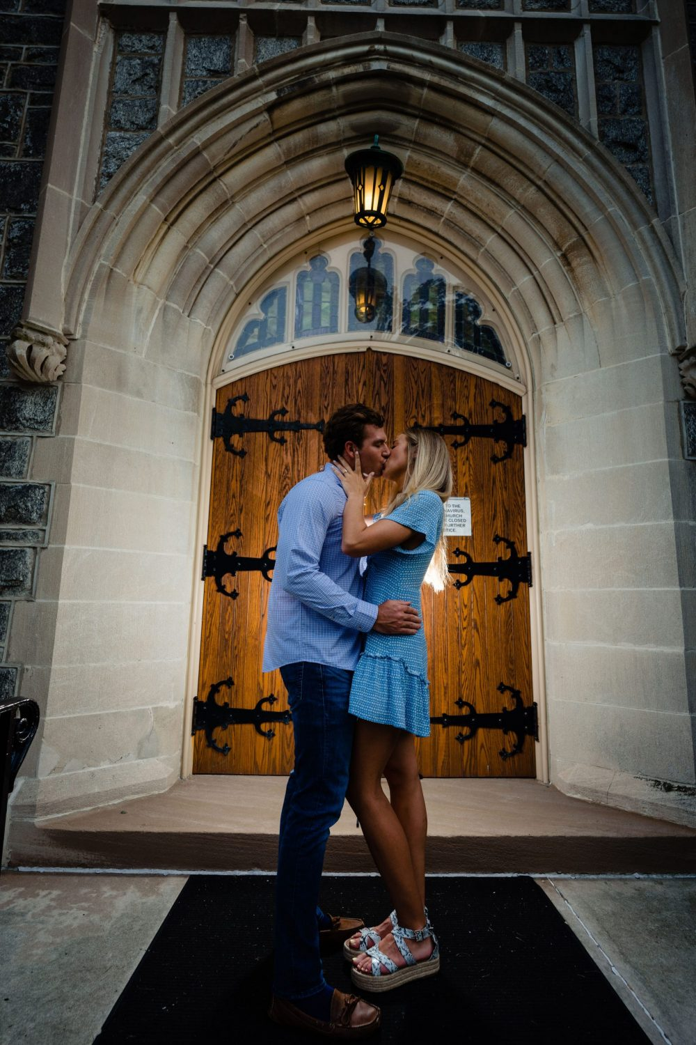 doors at First Presbyterian Church engaged couple kissing