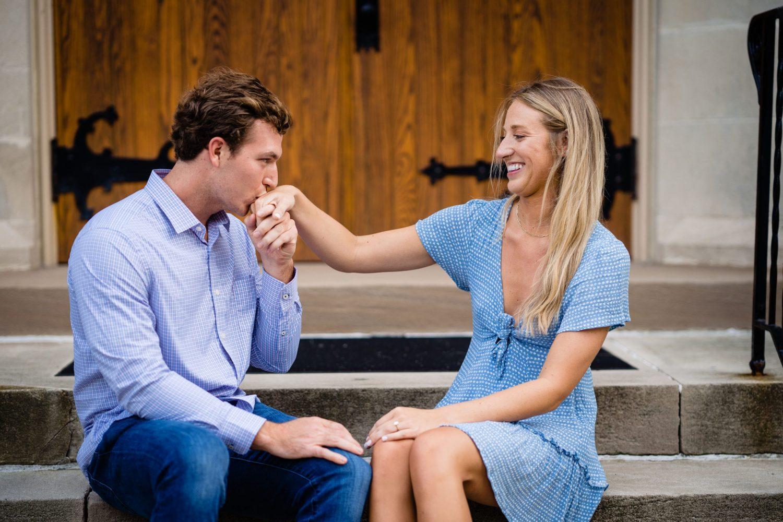 blue dress guy kissing fiancees hand