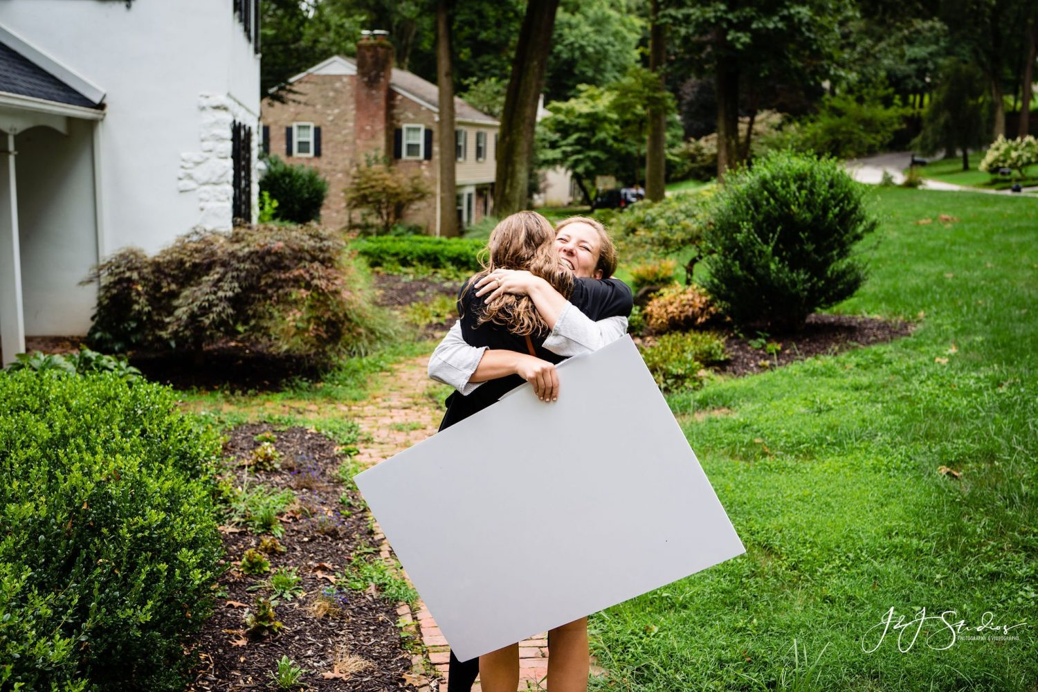 hugging girls with poster green grass