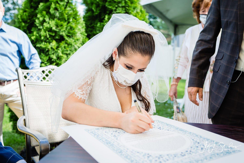 bride signs ketubah jewish wedding
