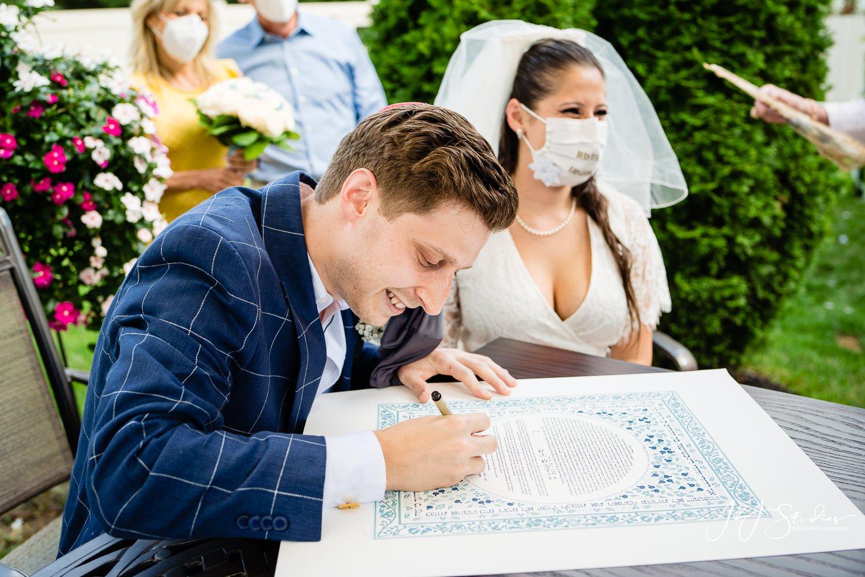 groom signs ketubah