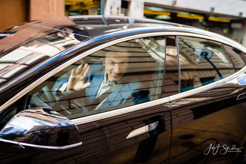 guy waving in Tesla
