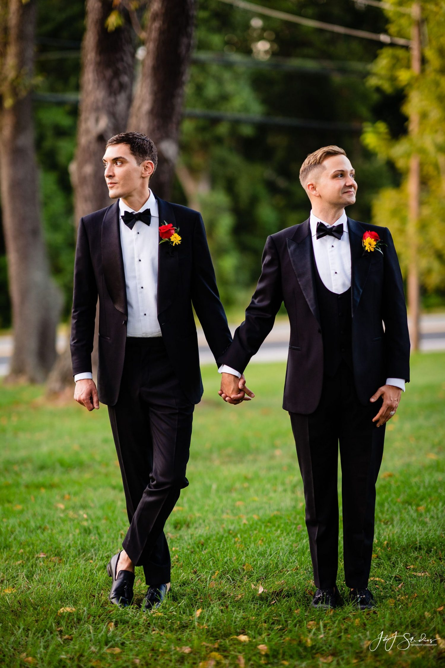 grooms holding hands outside