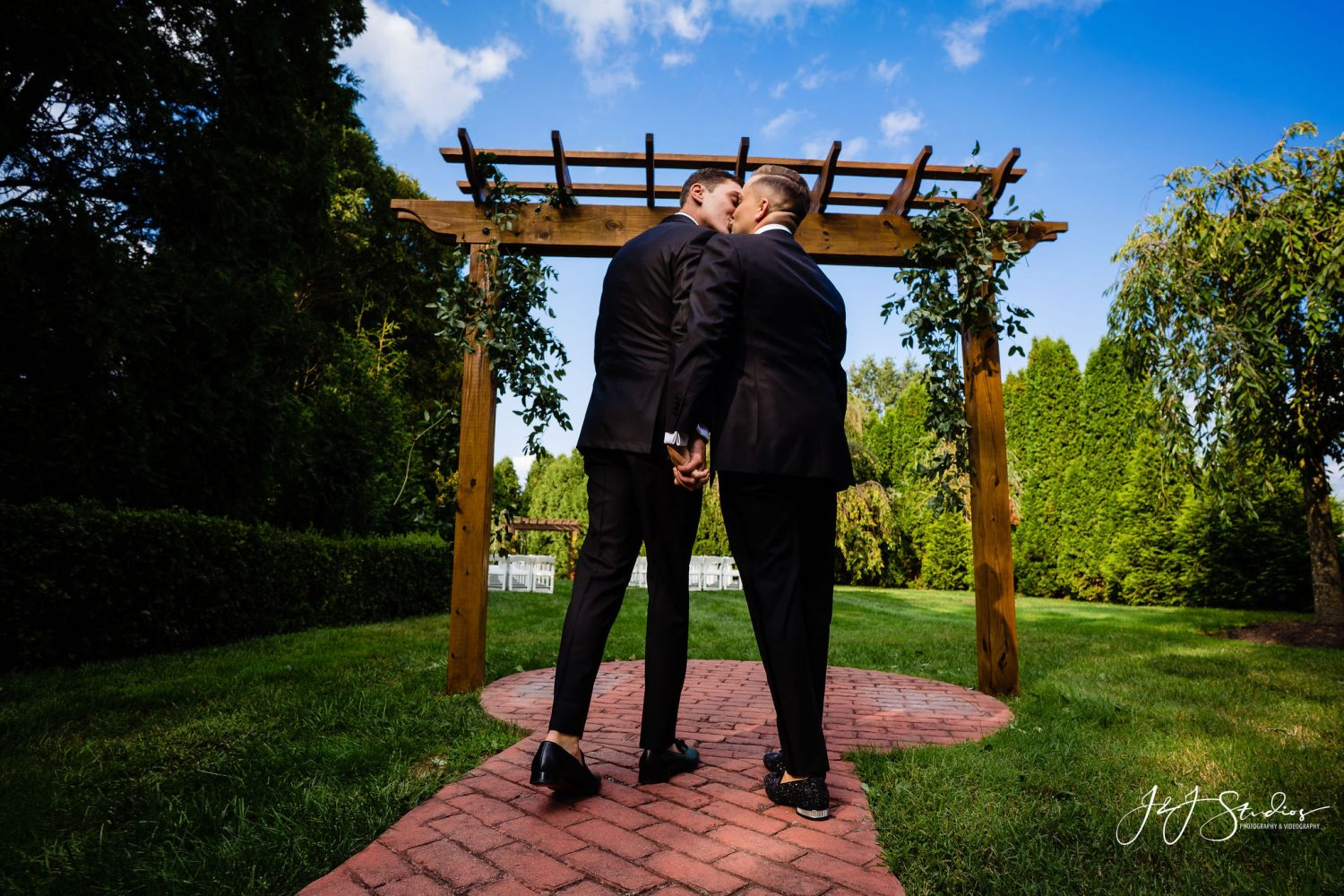 two grooms issing under wedding archway