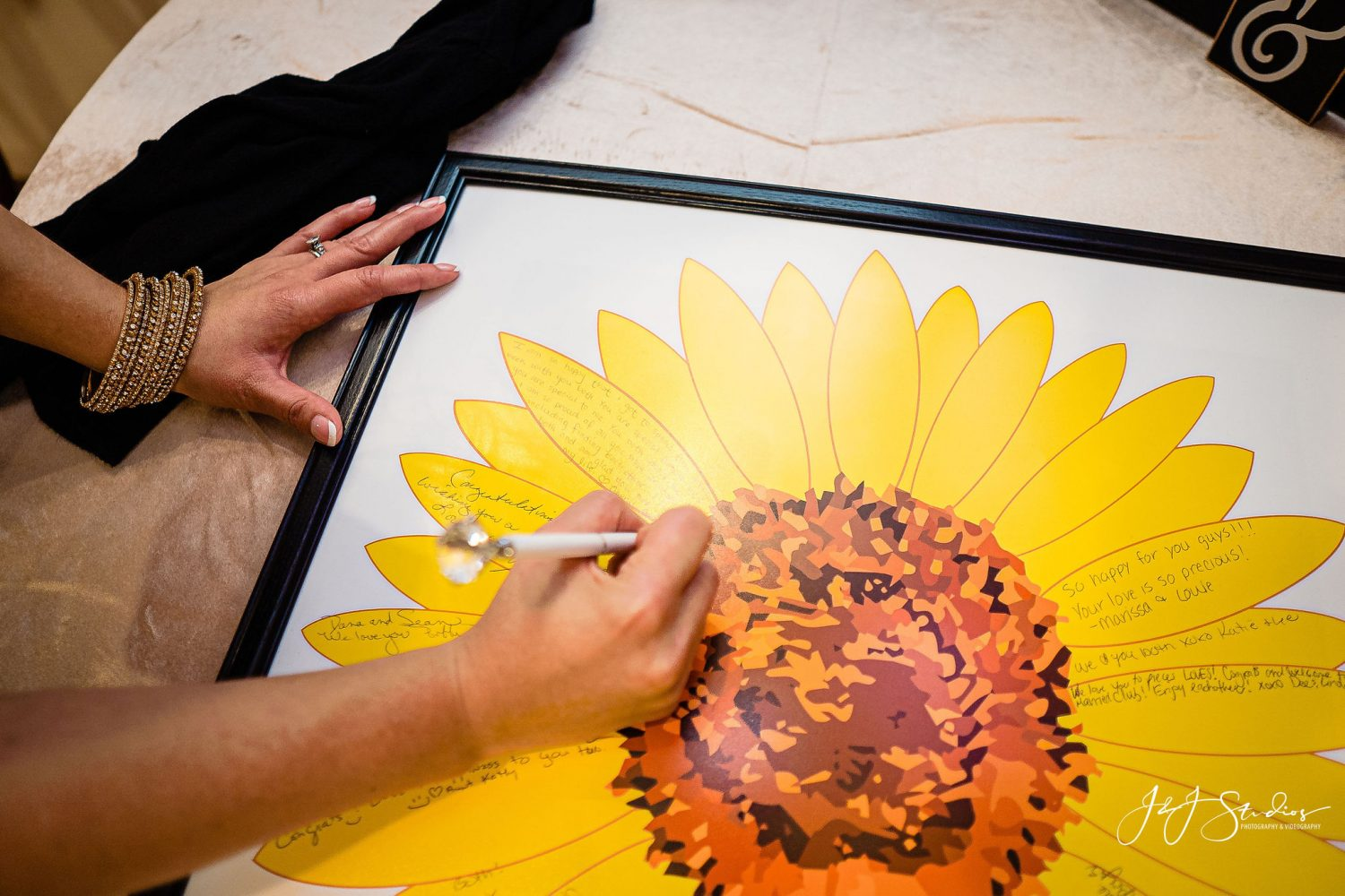 guests signing sunflower picture for wedding
