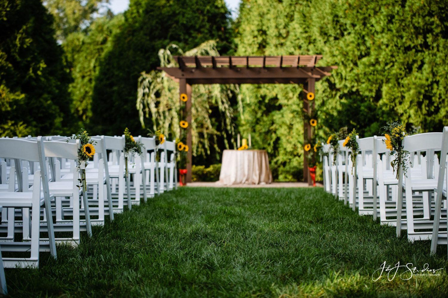 ceremony white chairs wooden arch