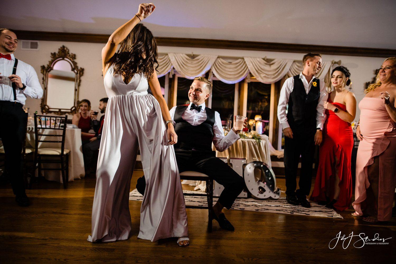 girl silver romper dancing guy in chair