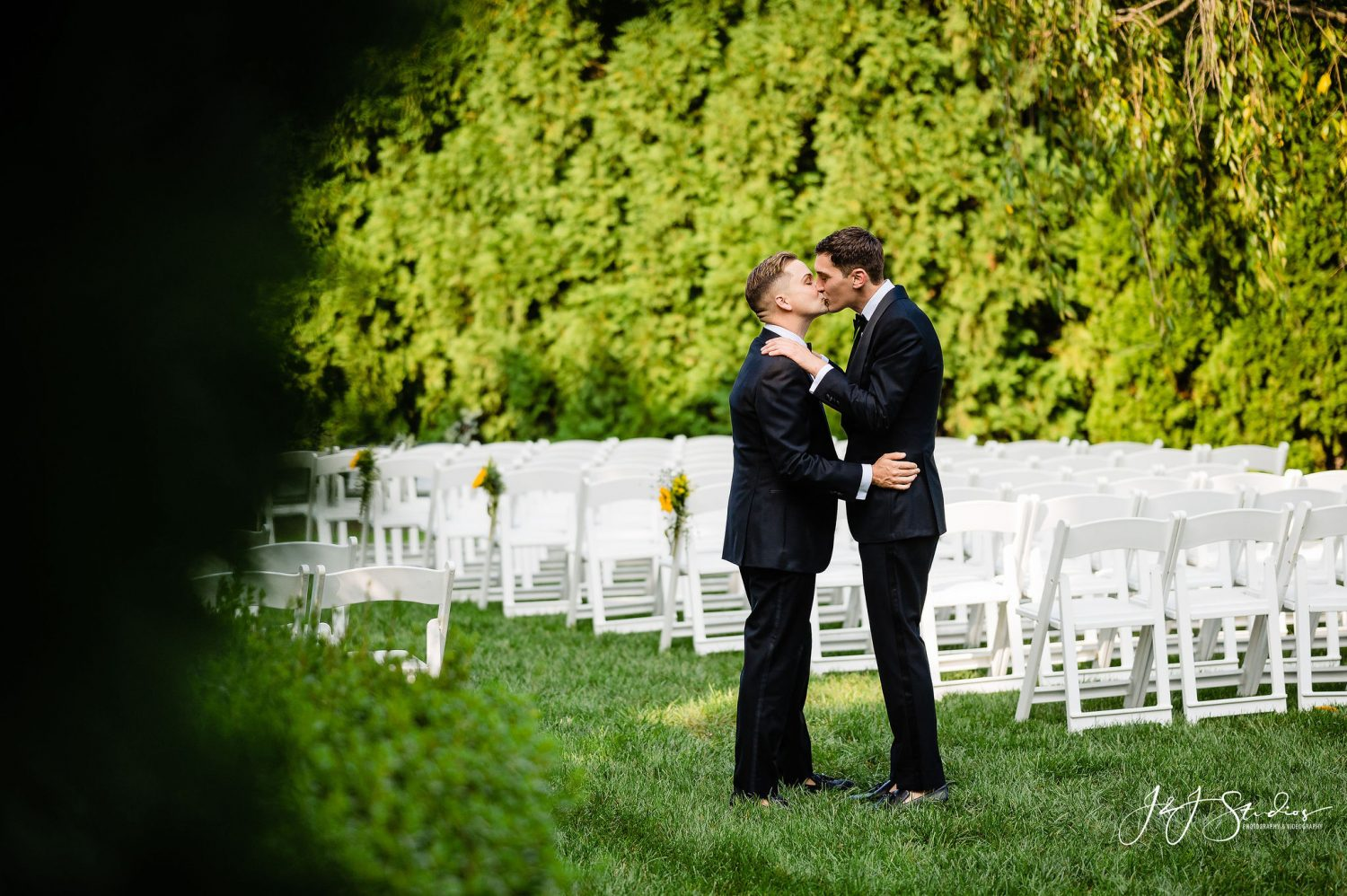 white chairs two newlyweds kissing