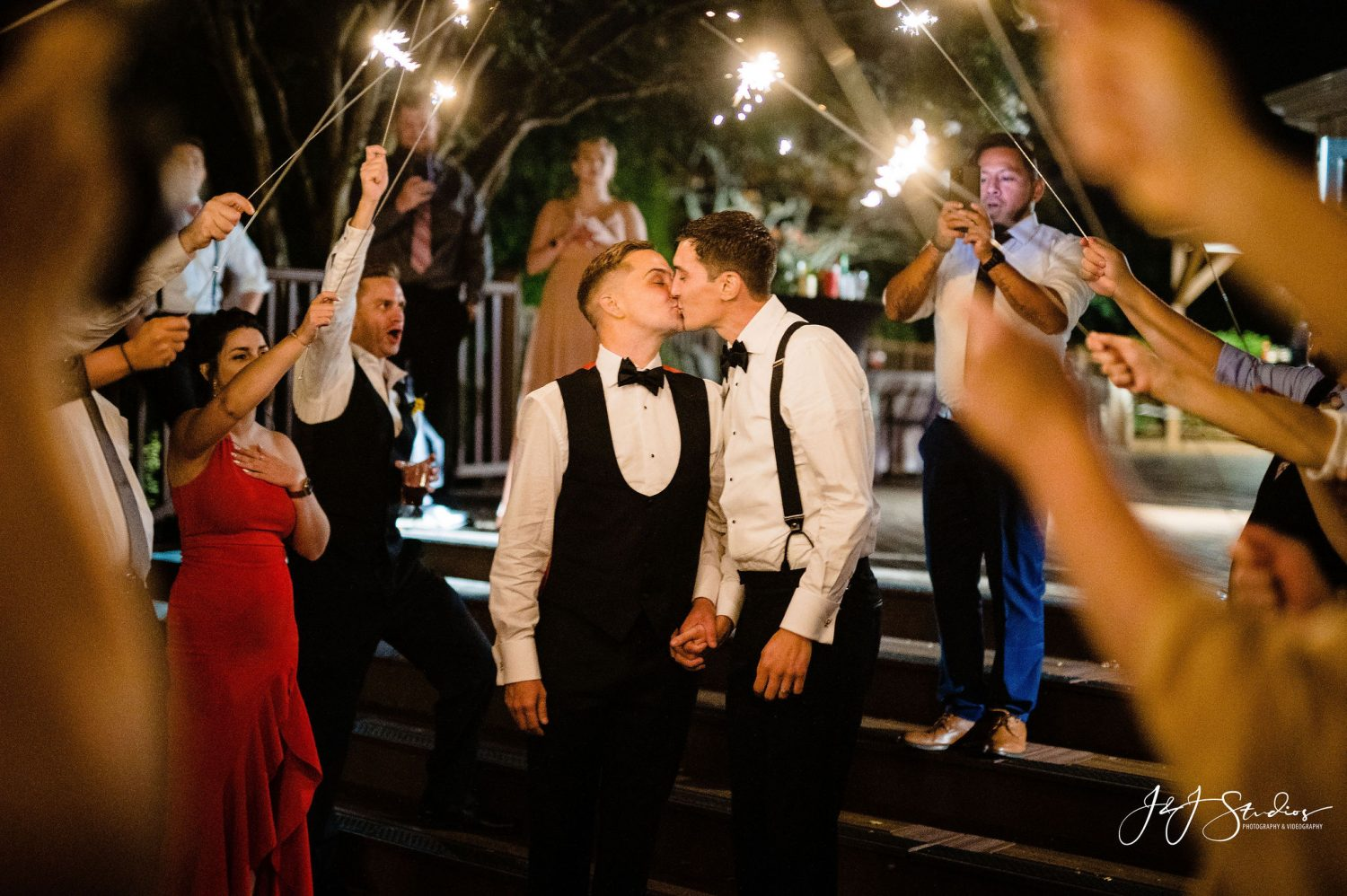newlyweds bowties kissing sparkler exit