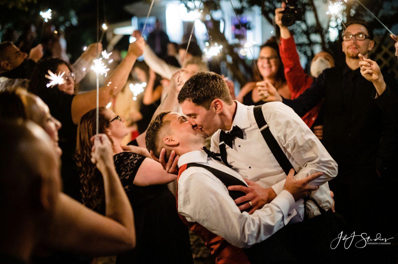 two men kissing sparklers wedding