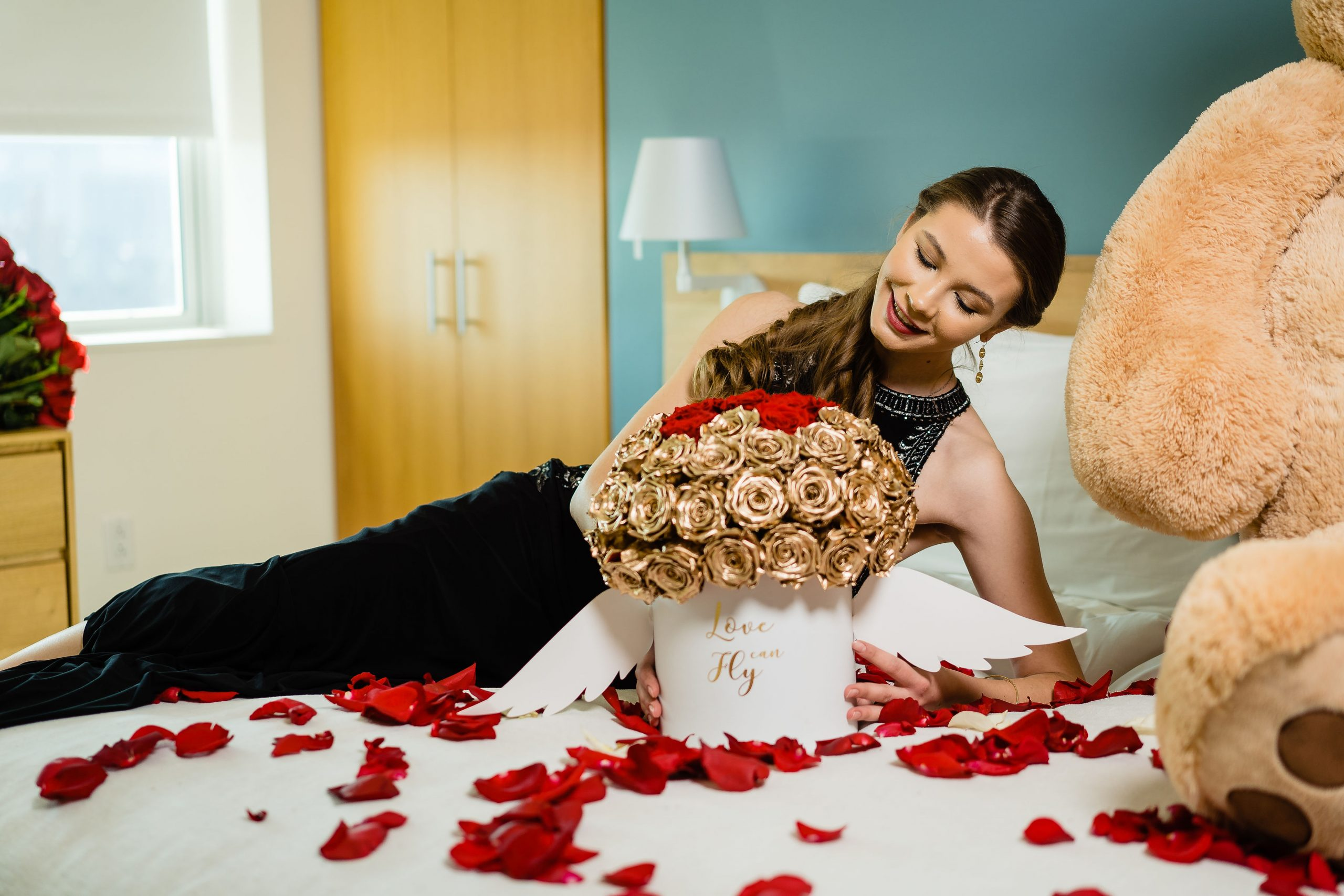 Woman lying on bed during flower boutique styled shoot