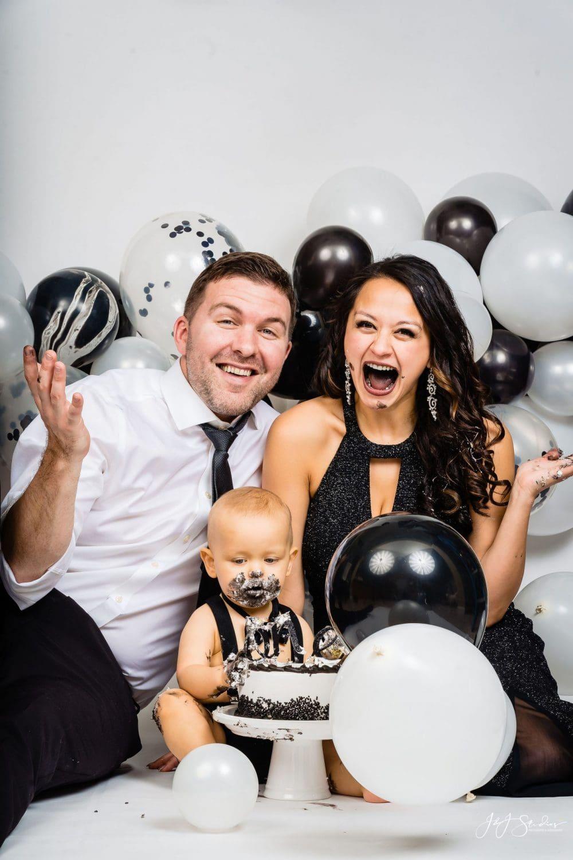 Happy parents smashing cake