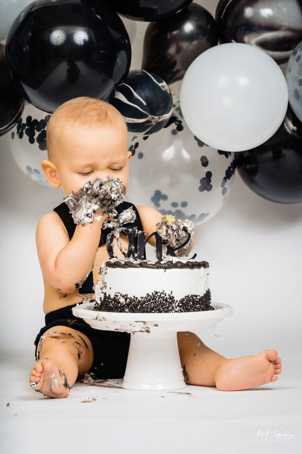 Baby enjoying First Birthday Cake Smash Session