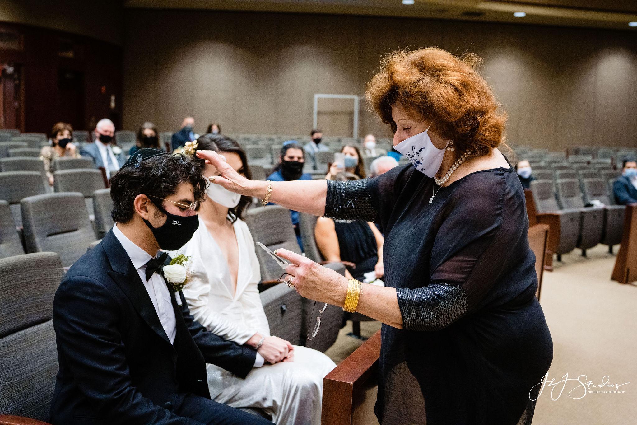 Woman  hand on groom's head during Jewish practice