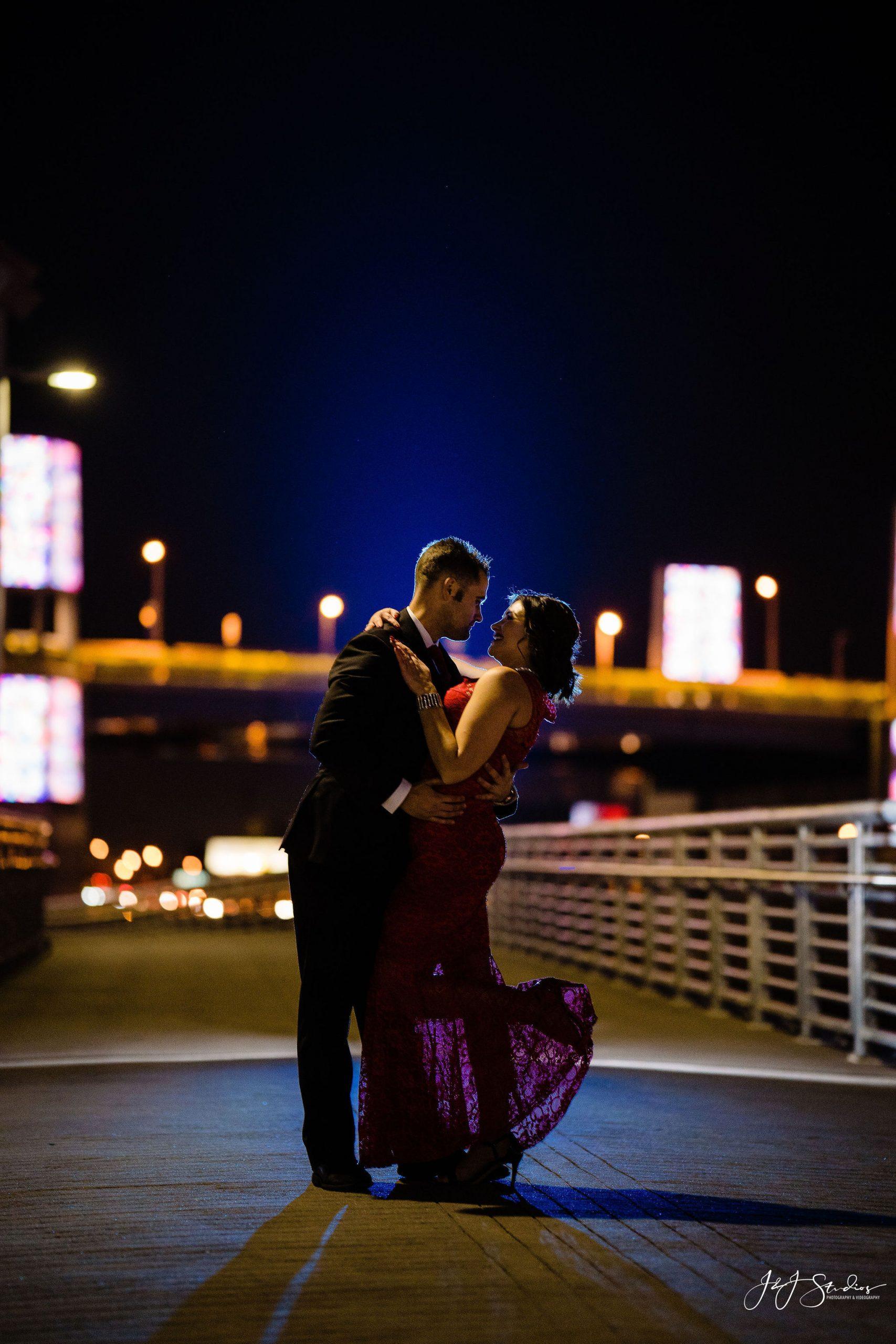 engaged couple night skyline dip