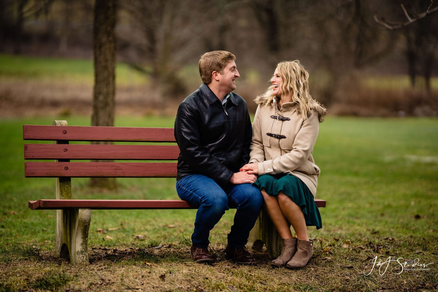 engaged couple bench laughing