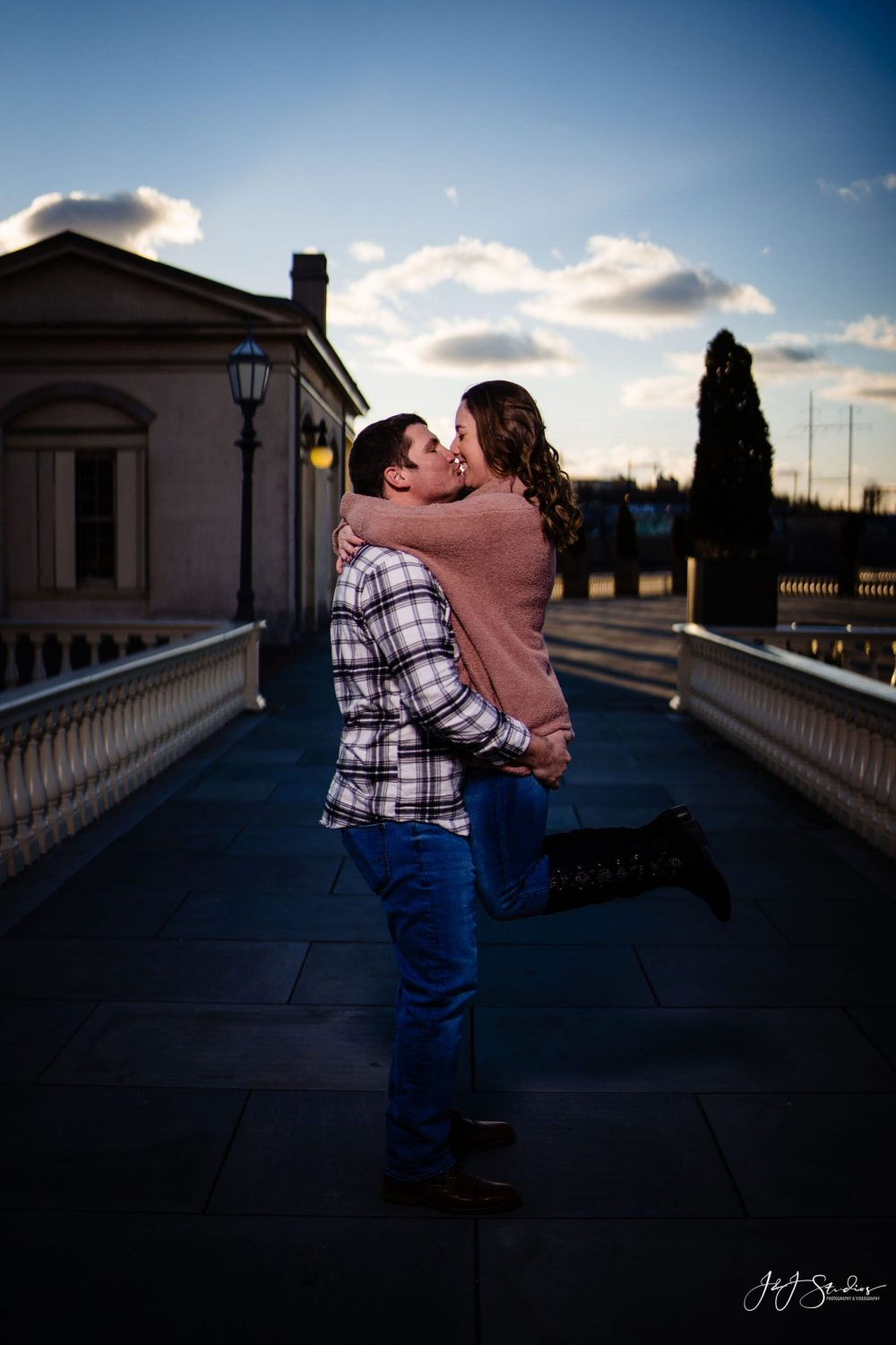 Woman jumps in man arms Boathouse Row Engagement Session