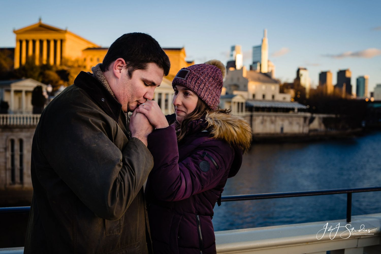 Man kising woman on her hand Boathouse Row Engagement Session