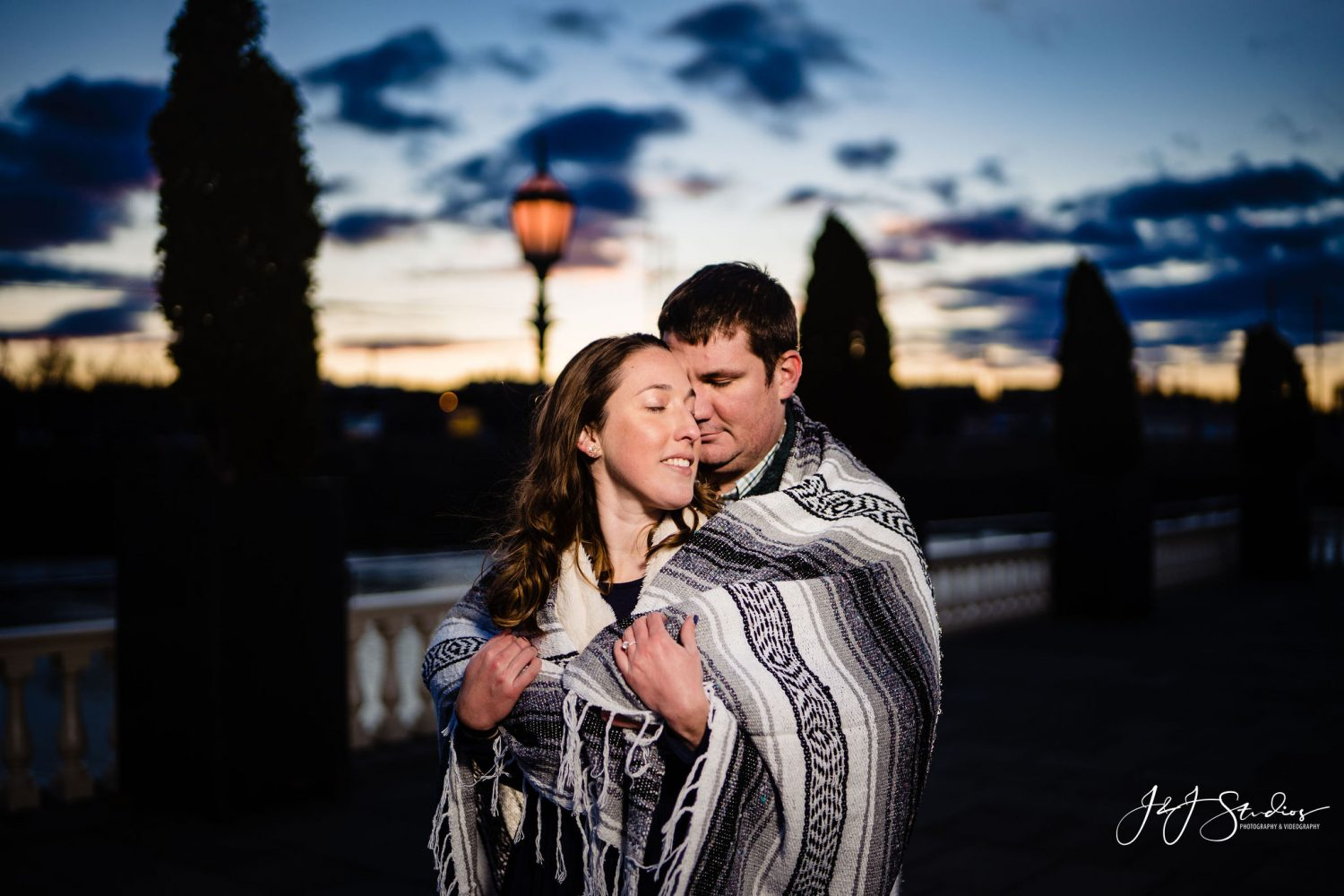 Woman wrapped in man's arms Boathouse Row Engagement Session