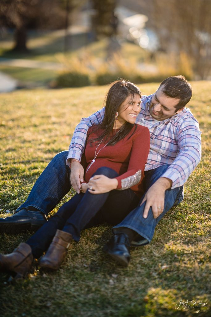 couple sitting in grass maternity