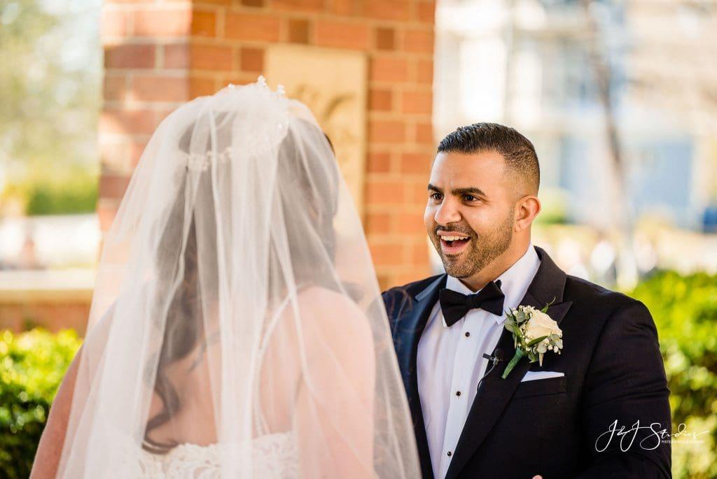 happy groom first look reaction