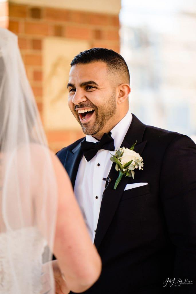 happy groom first look react