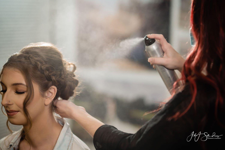 Not your average bella spraying hairspray in her hair