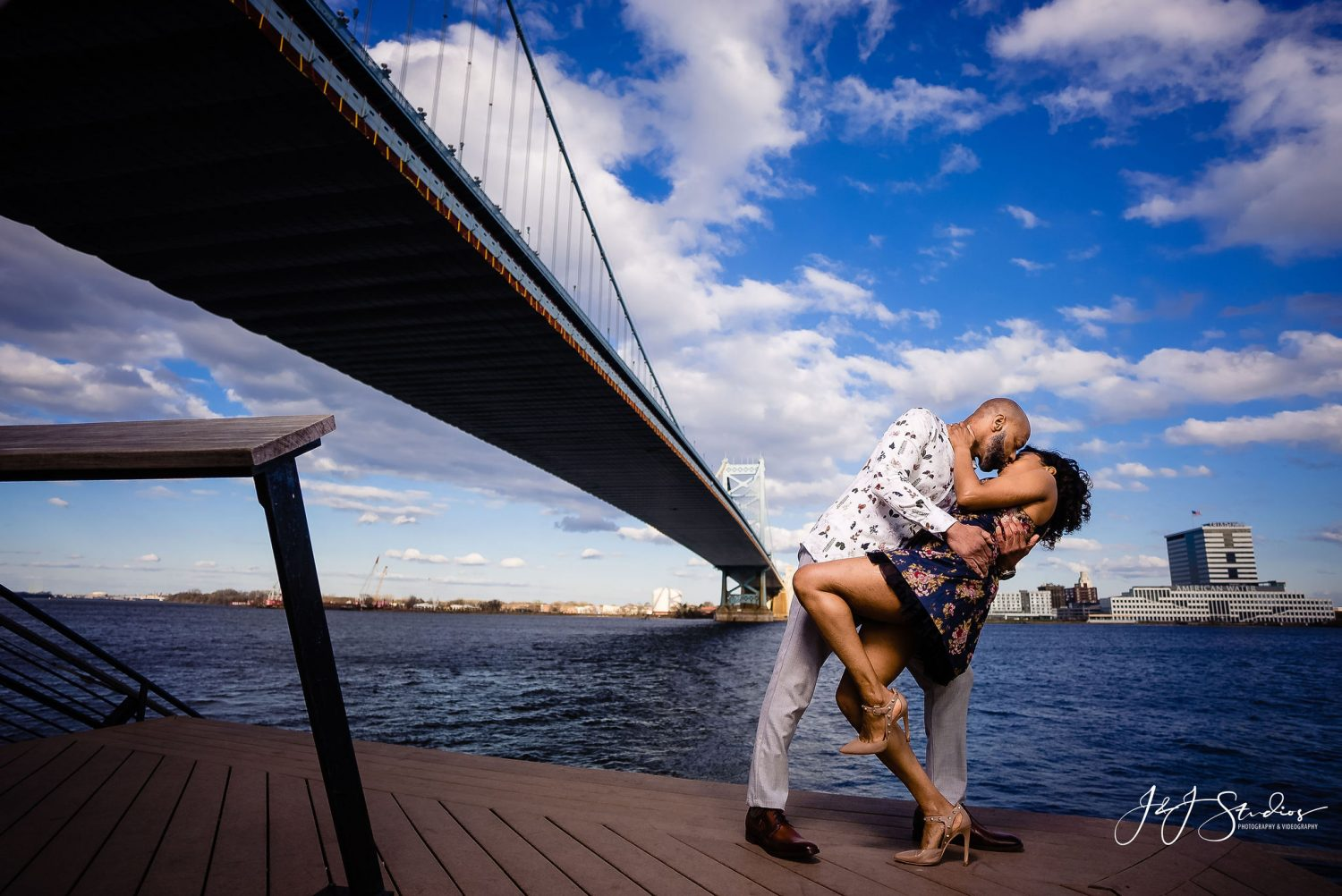 Man and woman under the bridge Downtown Philly Engagement