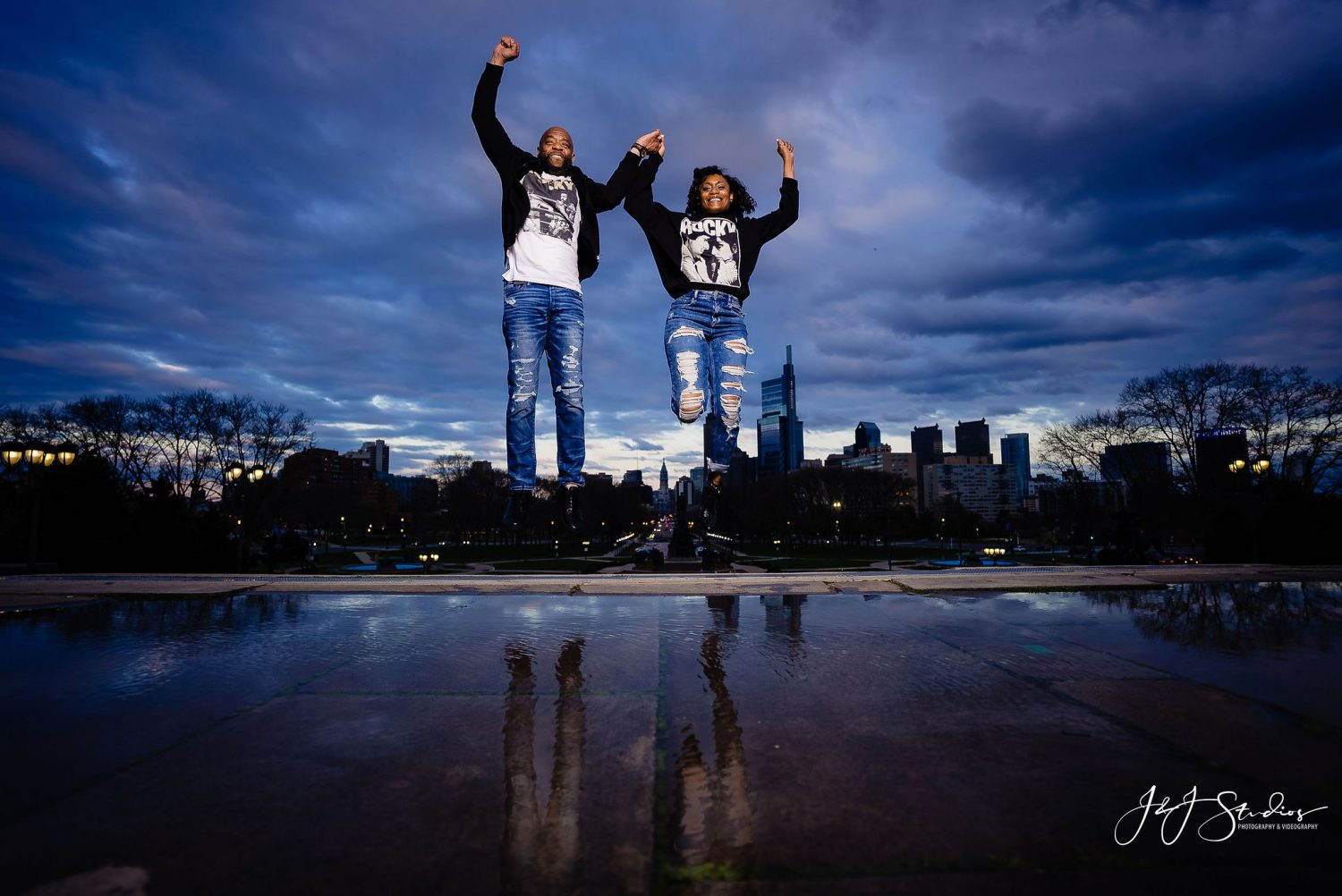 Couple jumping in the air Downtown Philly Engagement