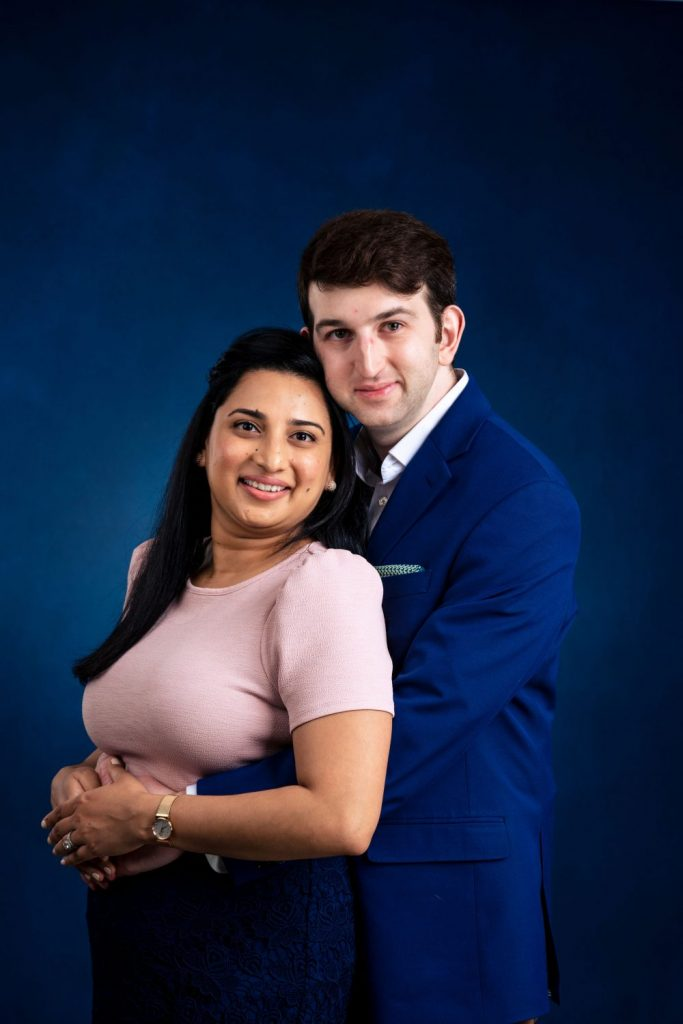 professional couple man holding woman from behind looking at camera