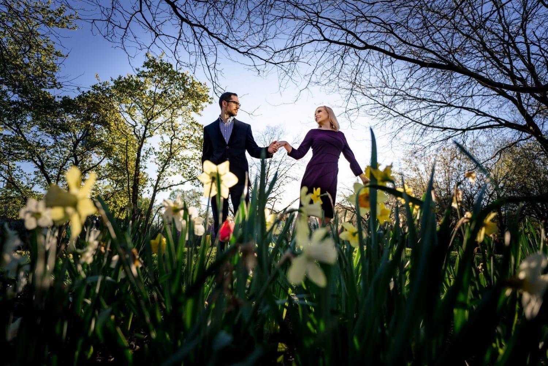 Couple holding hands near flowers Boathouse Row Philadelphia and Art Museum