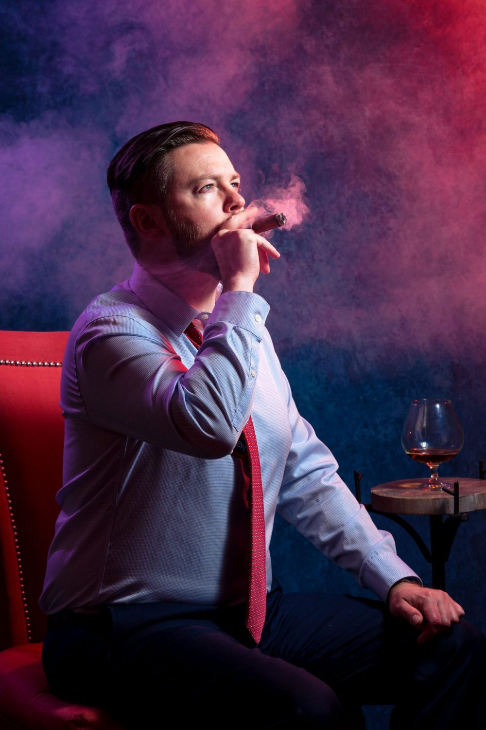 Man smoking in red chair Groom Cigar And Shots