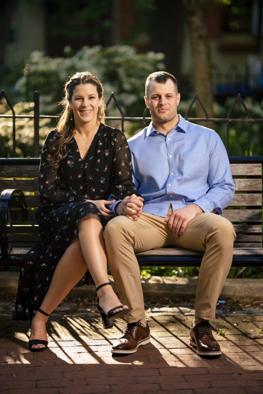 Engaged couple sitting on bench