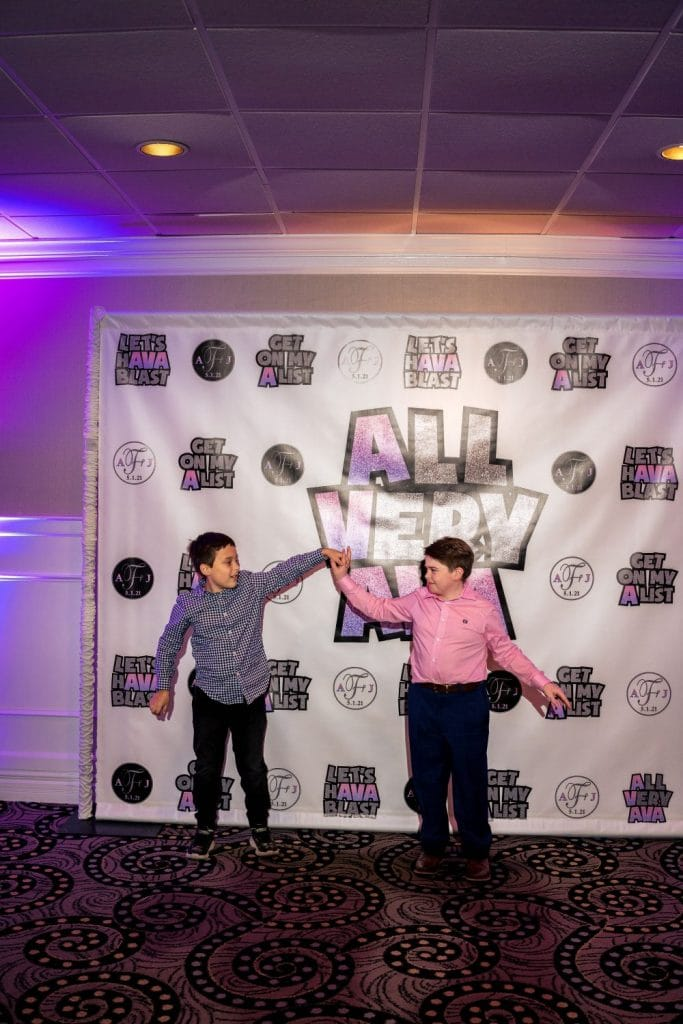 boys dancing in front of custom backdrop