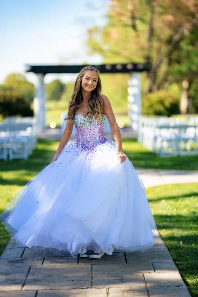 girl in ball gown in front of chairs