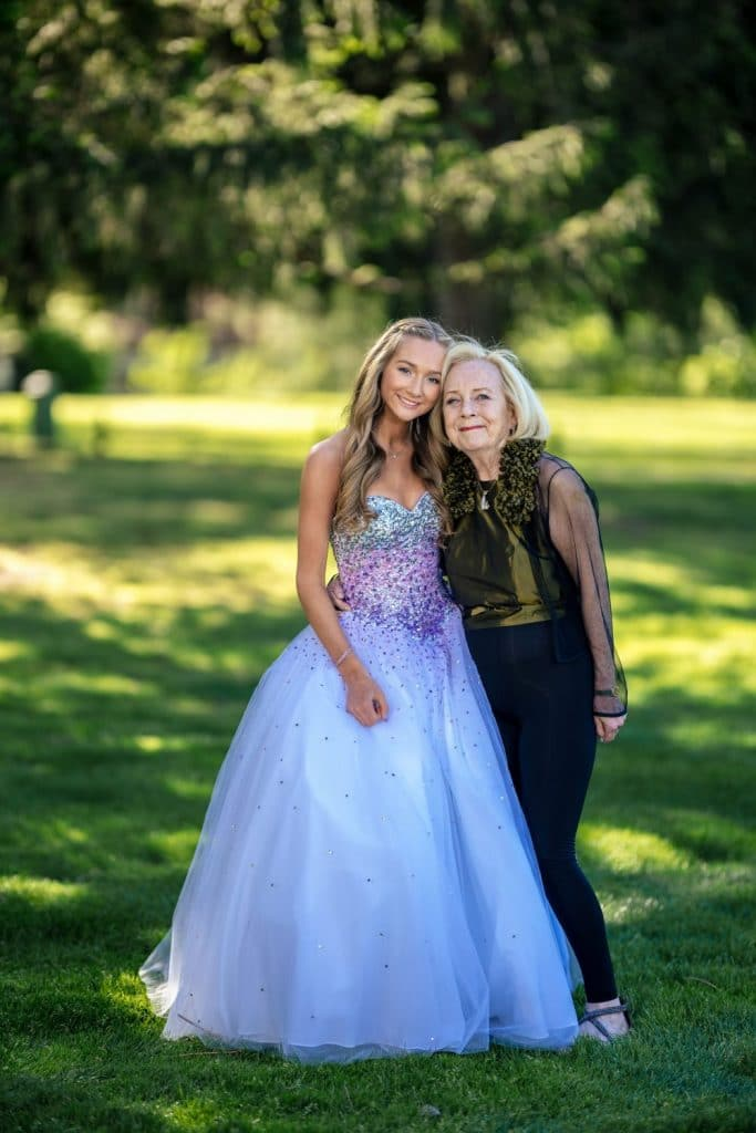 girl in ball gown and grandmother under trees