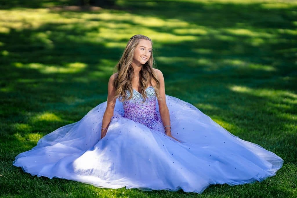 girl in ball gown sitting on the grass with dress around her